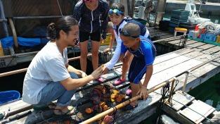 ヒオウギ貝を受け取る子どもたち